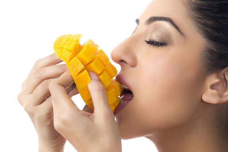 Mujer comiendo mango